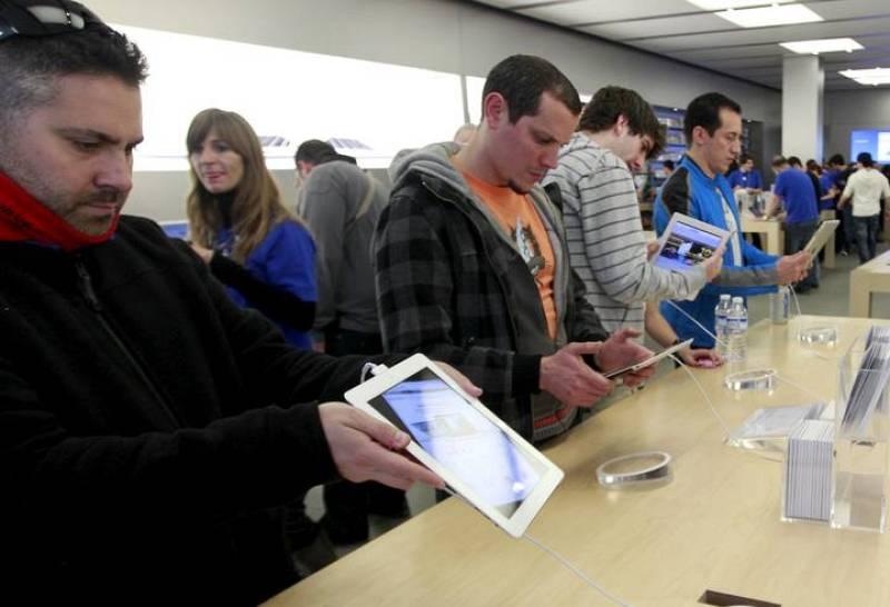 Varias personas observan el Ipad 2, la nueva tableta electrónica de Apple que desde esta tarde está disponible en los establecimientos que habitualmente venden estos productos