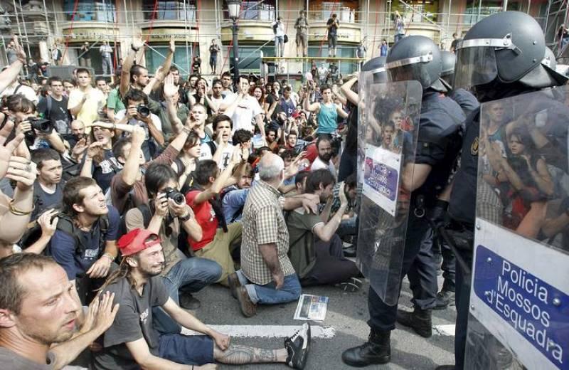 Muchos jóvenes permanecen sentados ante los policías antidisturbios