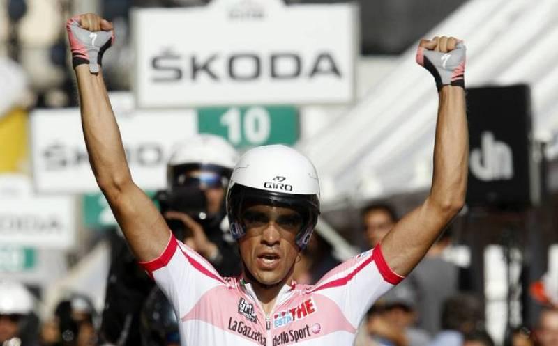 El líder del Giro entra en meta con los brazos en alto.