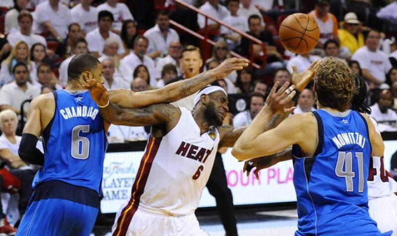 El jugador Tyson Chandler (c) de los Mavericks de Dallas en acción ante la defensa de Mike Miller (i) y Eddie House (d) de los Heat de Miami durante el sexto juego de la NBA.