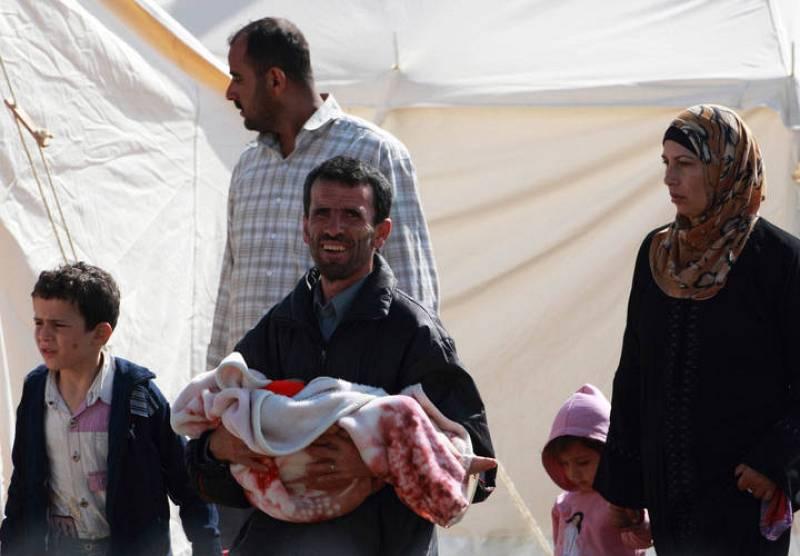 Una familia de refugiados, en las tiendas del campo de refugiados de Boynuegin.