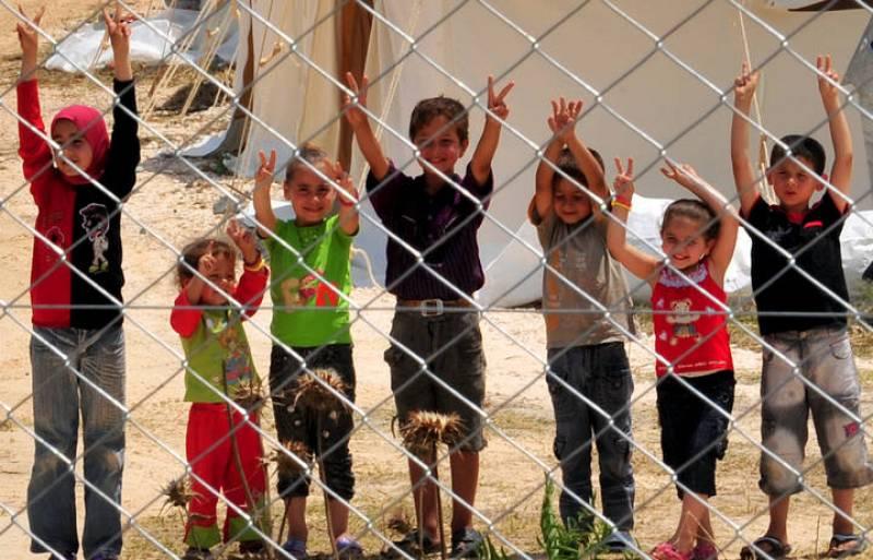 Un grupo de niños saluda desde un campo de refugiados en Turquía.