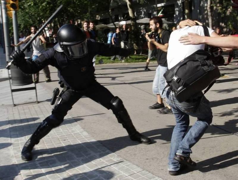 Uno de los antidisturbios golpea a un manifestante ante la puerta del Parlament