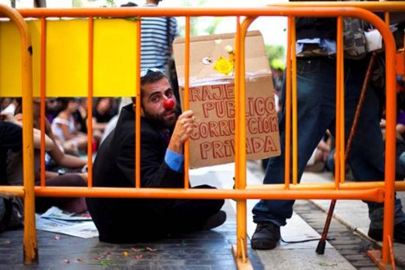 """Un manifestante con naríz de payaso con una pancarta con el mensaje """"traje público corrución privada""""."""