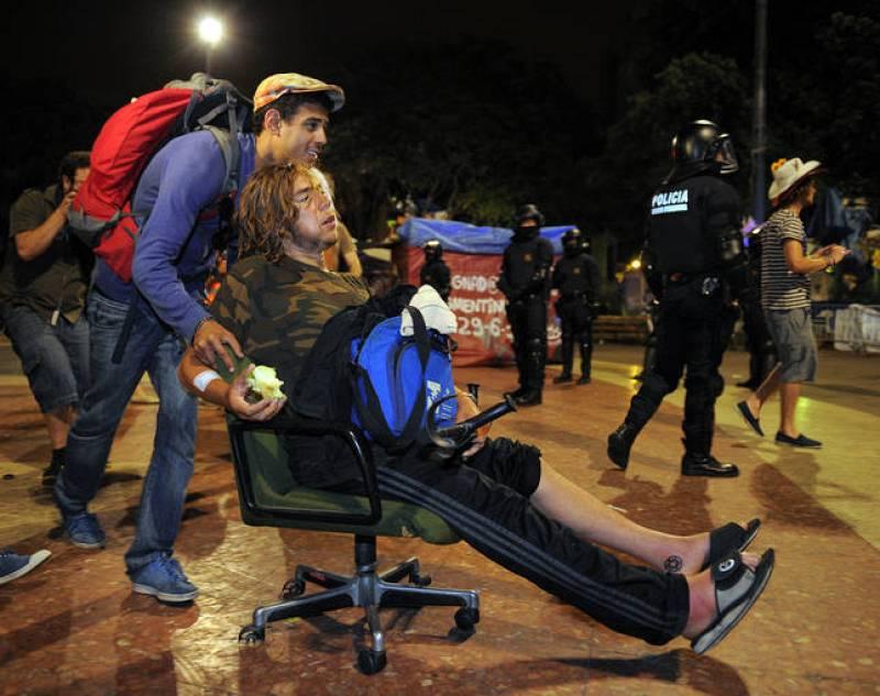 Un 'indignado' acarrea con otro empujándole en una silla de ruedas tras el ultimátum de la policía