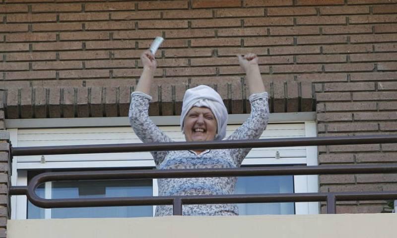 Una señora desde el balcón celebra que le ha tocado el quinto premio de la Lotería de Navidad.