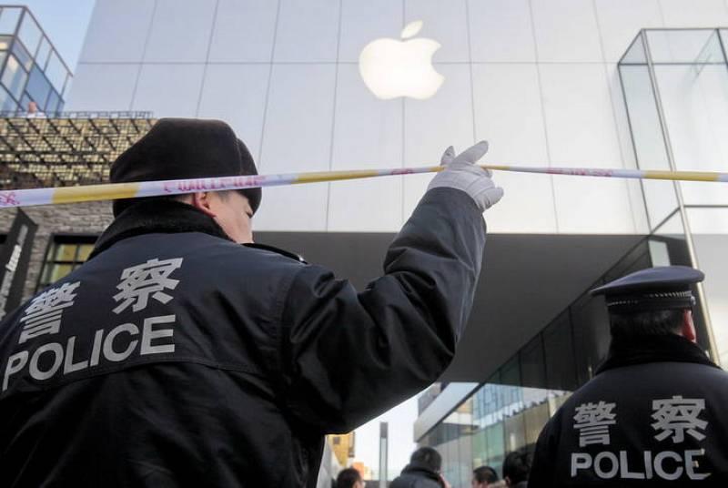 Policías chinos acordonan el exterior de una tienda Apple mientras un grupo de personas espera comprar el nuevo iPhone 4S
