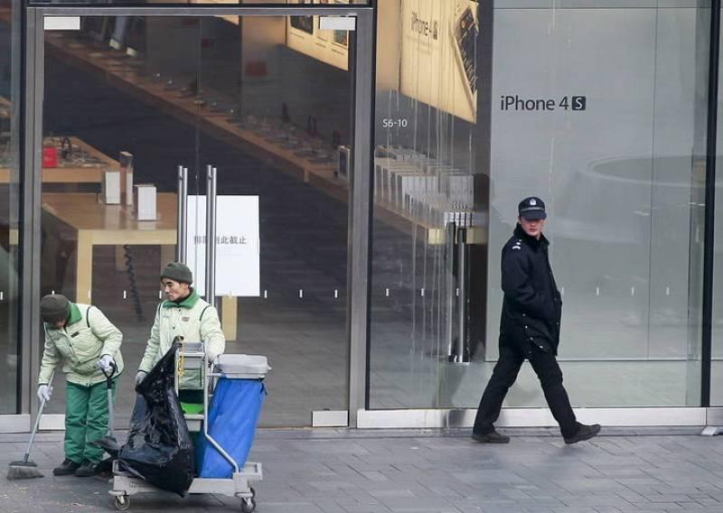 Un policía observa a trabajadores que limpian en el exterior de una tienda Apple después de los incidentes provocados por un grupo de personas que hacía cola comprar el nuevo iPhone 4S