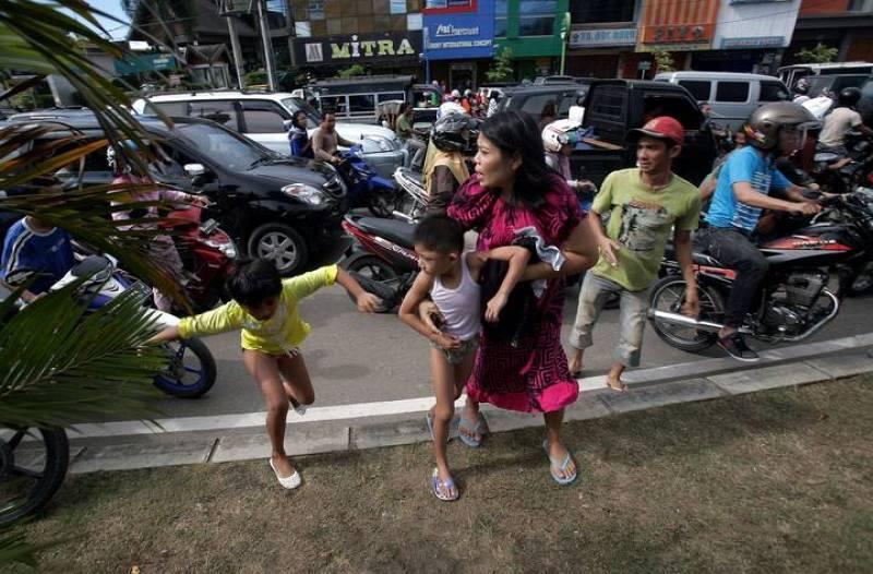 Una familia indonesia corre tras el primer temblor, que ha provocado una alerta de tsunamis en todo el Índico