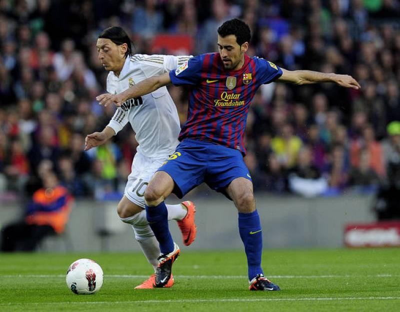 El alemán Mesut Özil pugna en el centro del campo un balón con Sergio Busquets