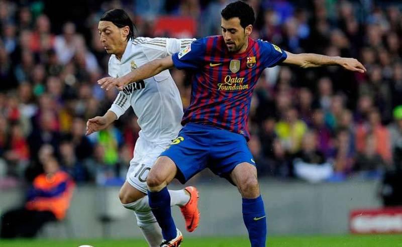 Busquets forcejea con Özil por el balón.