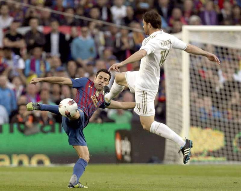 El centrocampista del FC Barcelona Xavi Hernández (i), pelea un balón con el centrocampista del Real Madrid Xabi Alonso