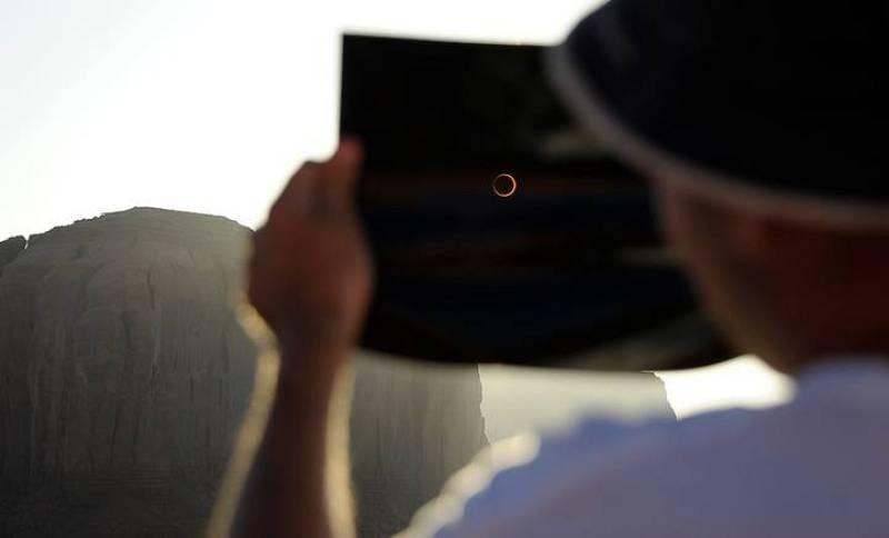 Un aficionado disfruta del eclipse de sol mirando a través de una radiografía