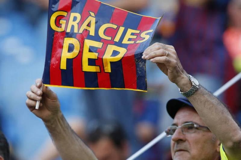 Un aficionado del FC Barcelona sostiene una pancarta de agradecimiento al entrenador del equipo, Josep Guardiola.