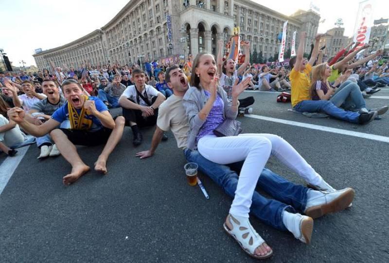 Aficionados disfrutan del partido en una pantalla gigante en la 'fan zone' de Kiev.