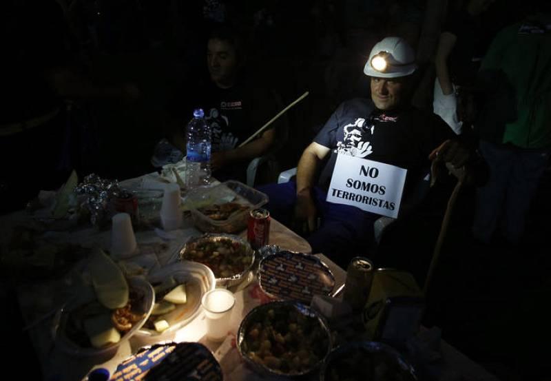 Un minero portando un cartel donde se peude leer que no son terroristas