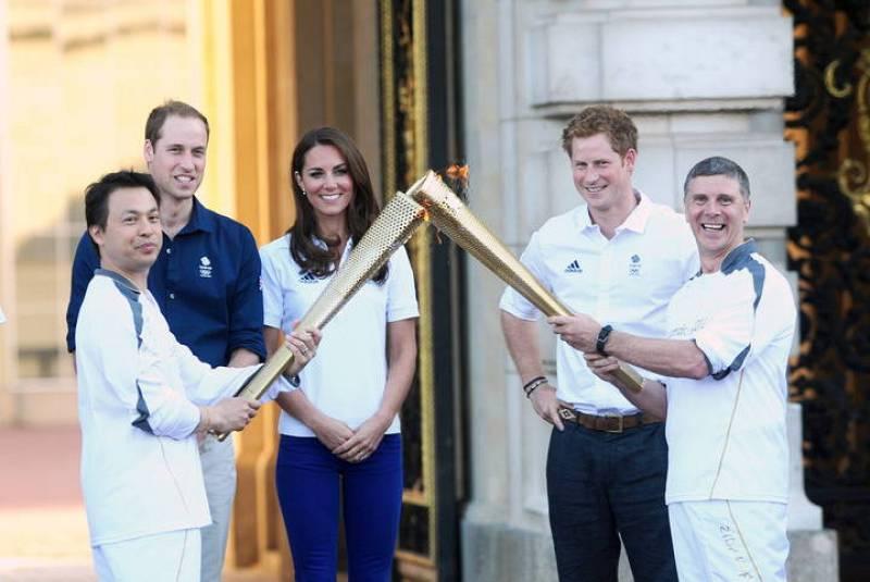 El duque  y la duquesa de Cambridge  y el príncipe Enrique observan el relevo de la antorcha olímpica de Londres 2012 entre Wai-Ming  y John Hulse en el palacio de Buckingham en Londres (Reino Unido).