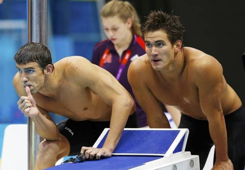Michael Phelps and Nathan Adrian of the U.S. watch a swimmer during the men's 4x100m freestyle relay final during the London 2012 Olympic Games at the Aquatics Centre