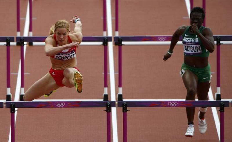 La austríaca Beate Schrott (L) compite con la nigeriana Seun Adigun en la primera ronda femenina de100 metros con vallas durante los Juegos.