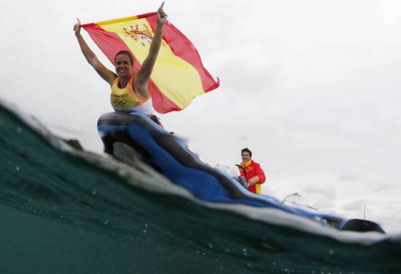 La española Marina Alabau celebra su victoria portando la bandera de España montada en su tabla de windsurf.
