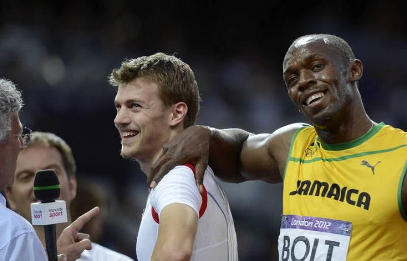 El atleta jamaicano Usain Bolt bromea con el francés Christophe Lemaitre tras las semifinales de los 200m masculinos.