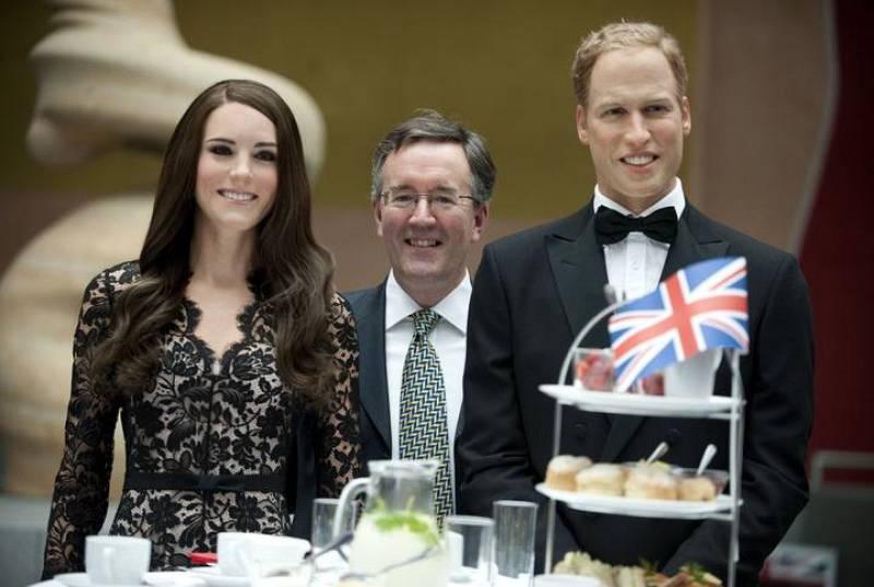 Los duques de Cambridge de cera posando con el viceembajador británico en Alemania, Andrew Noble