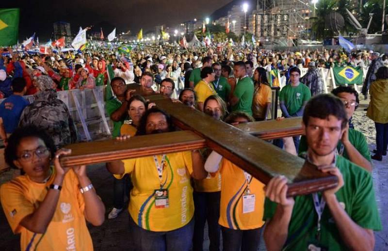 Un grupo de jóvenes transporta la Cruz de los Jóvenes, que ha presidido la misa inaugural de la JMJ en la playa de Copacabana, en Río de Janeiro, Brasil