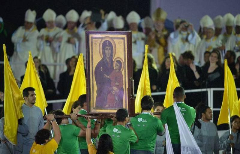Un grupo de fieles porta las imágenes de la Virgen María y Jesucristo que han presidido la eucaristía inaugural de la JMJ