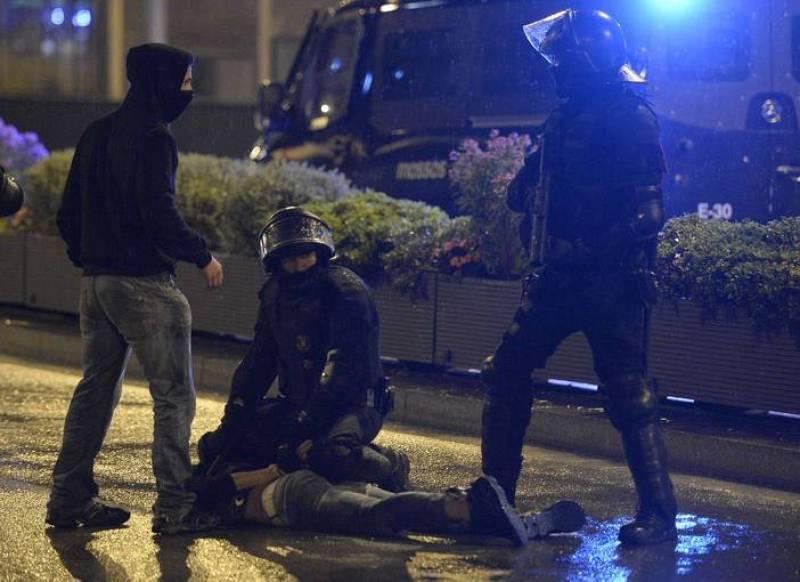 Un manifestante es detenido por la policía durante las protetas.