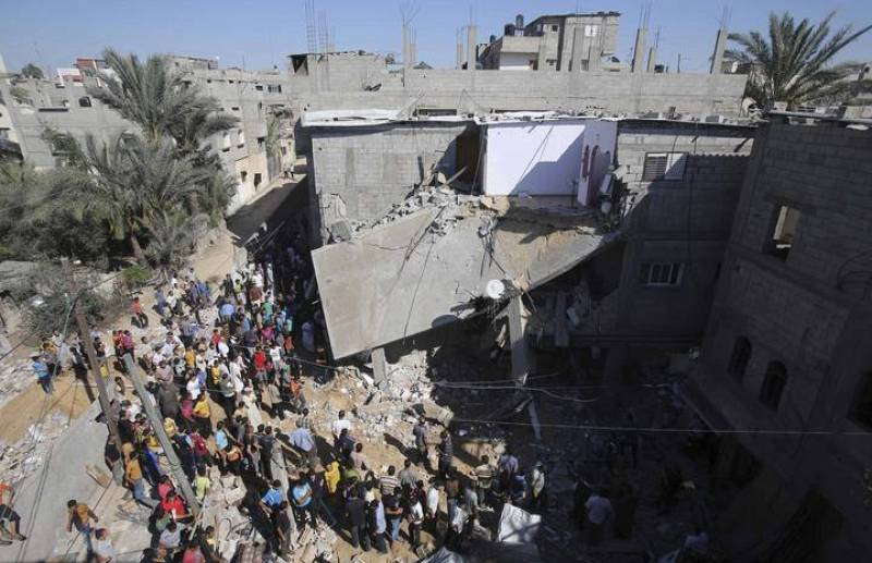 Palestinians gather around a house which police said was destroyed in Israeli air strikes in Khan Younis in the southern Gaza Strip