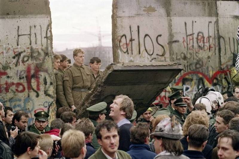 Una fotografía de noviembre de 1989 muestra a una multitud de berlineses occidentales delante del Muro de Berlín, mientras los guardias fronterizos de Alemania Oriental demuelen una sección de la pared.