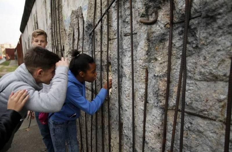 Varios niños miran a través de un agujero de la antigua frontera del Muro de Berlín en la Bernauer Strasse, en Berlín.