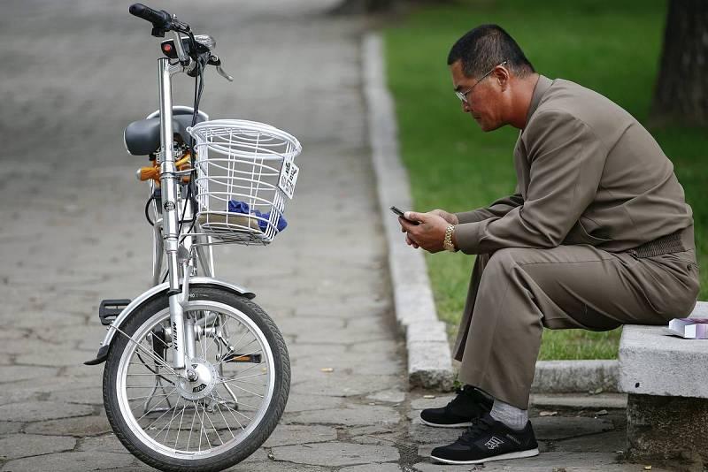 Un hombre junto a una bicicleta eléctrica utiliza un teléfono móvil en el centro de Pyongyang. Signos de modernidad en la capital de Corea del Norte cuando prepara el 70 aniversario del Partido de los Trabajadores