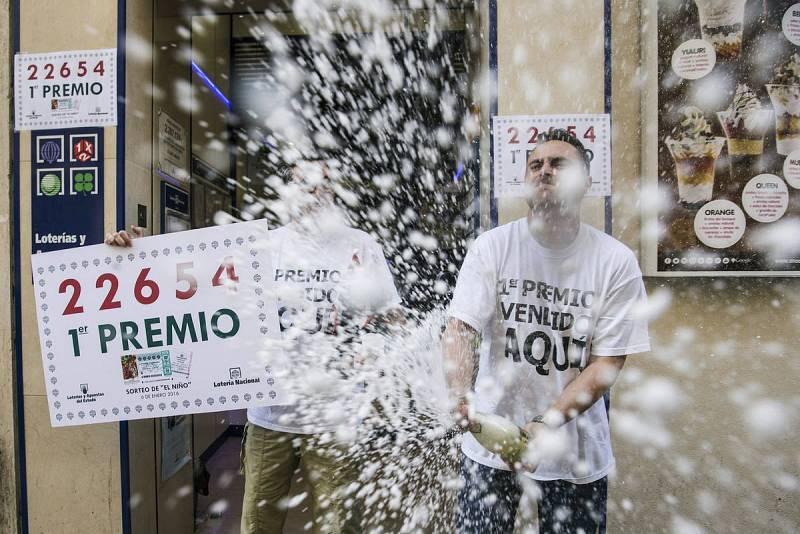 """El trabajador Miguel Ponce, de la Administración """"El Gato Negro"""" celebra el primer premio del sorteo extraordinario de la lotería de El Niño, del que ha vendido una serie."""