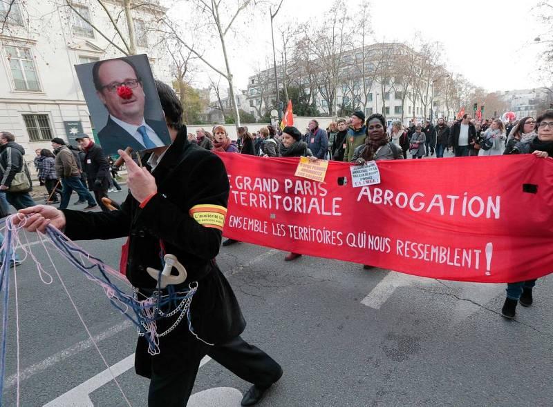 Un manifestante sostiene un retrato de Hollande con una nariz de payaso