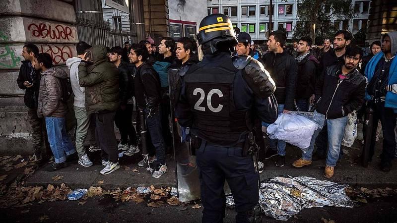 Policías antidisturbios ante una fila de migrantes cerca de las estaciones de metro de Jaures y Estalingrado, en París.