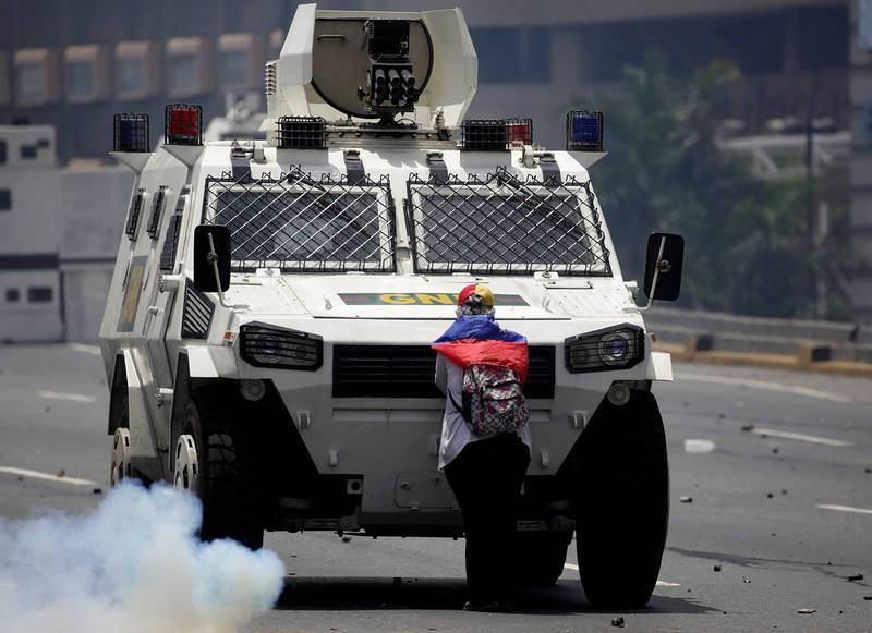 Una manifestante de la oposición bloquea una tanqueta de la Policía durante la manifestación contra Maduro en Caracas, Venezuela