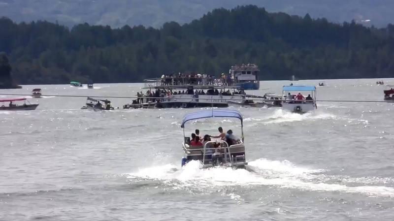 Numerosas lanchas se acercan a socorrer al barco turístico medio hundido.