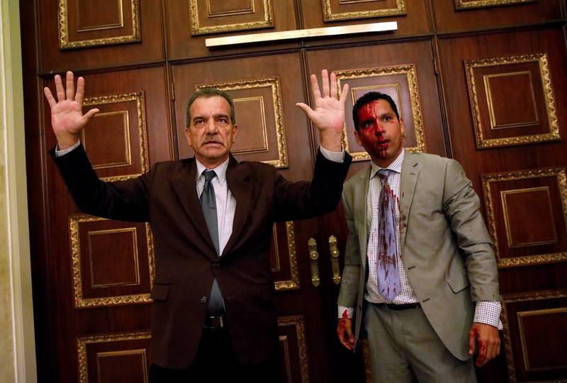 Los diputados de la oposición Luis Stefanelli, a la izquierda con los brazos en alto, y Leonardo Regnault, ensangrentado, durante el asalto a la Asamblea Nacional.