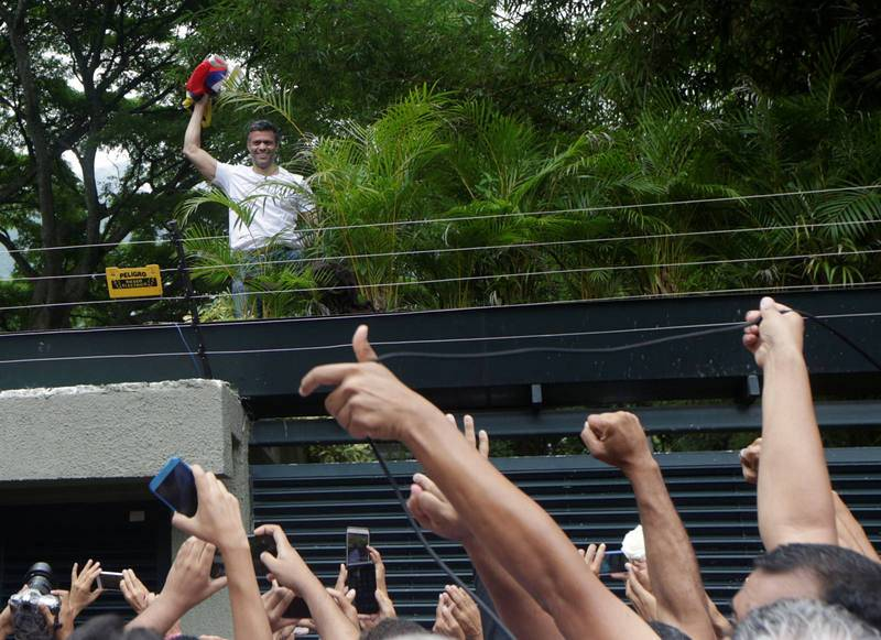 El líder opositor venezolano saluda a sus simpatizantes desde la valla de su casa, en la que permanece en arresto domiciliario