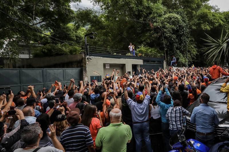 El opositor venezolano Leopoldo López saluda a seguidores desde dentro de su residencia en Caracas