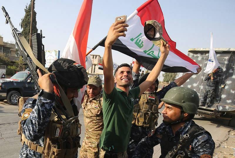 Un civil tomando una foto con su móvil junto a miembros de la policía federal que celebran la victoria en la Ciudad Vieja de Mosul