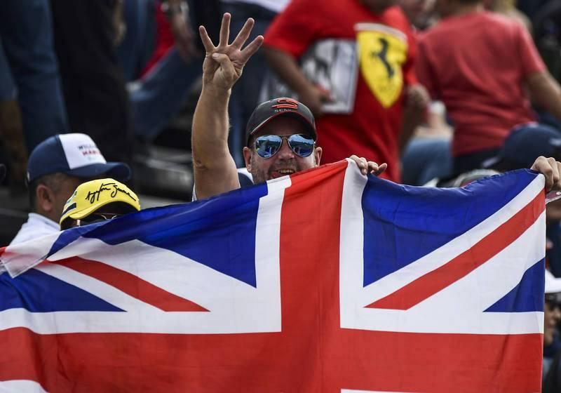 Un aficionado muestra cuatro dedos, número de campeonatos que ha logrado Hamilton.
