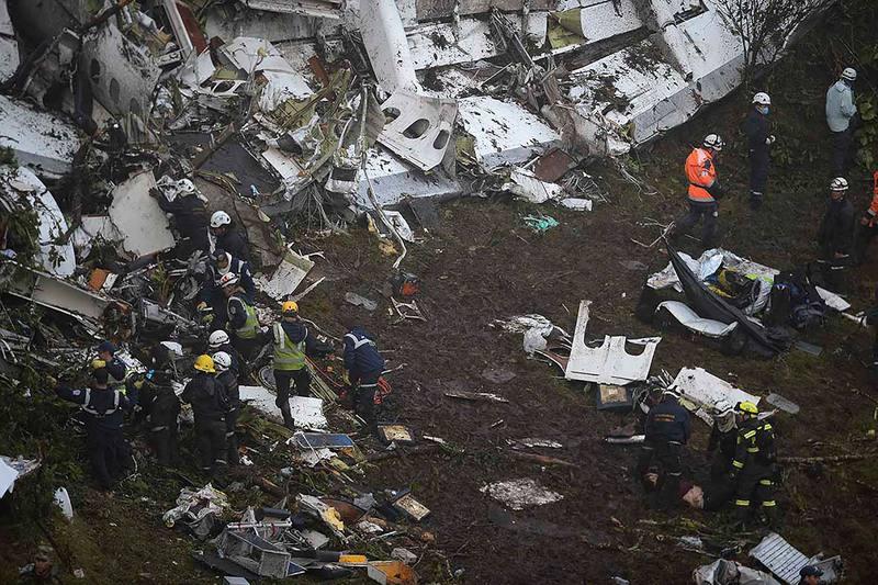 Miembros de los equipos de rescate inspeccionan el fuselaje del avión de LAMIA siniestrado en Colombia.