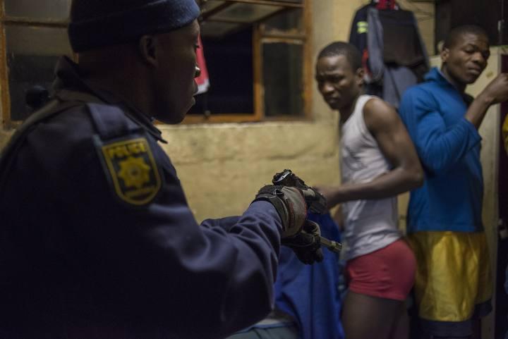 Un agente de la policía sudafricana apunta con su pistola a dos de los habitantes del albergue de trabajadores de Jeppestown, en Johanseburgo.