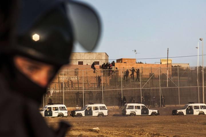 Agentes de la Guardia Civil escalan la valla fronteriza de Melilla para evitar el asalto de los inmigrantes subsaharianosia civil