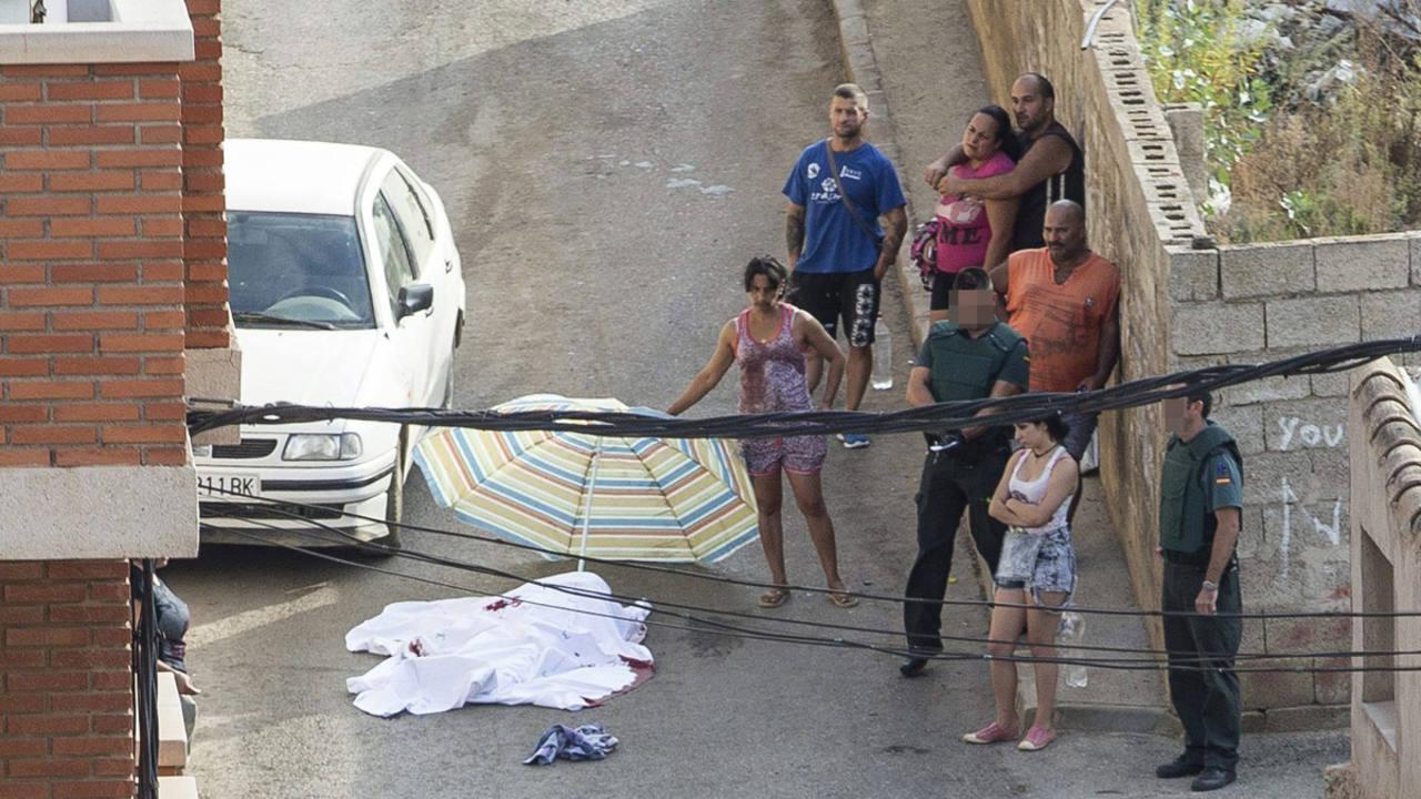 Agentes de la Guardia Civil y vecinos junto al cadáver de una mujer fallecida tras la riña.