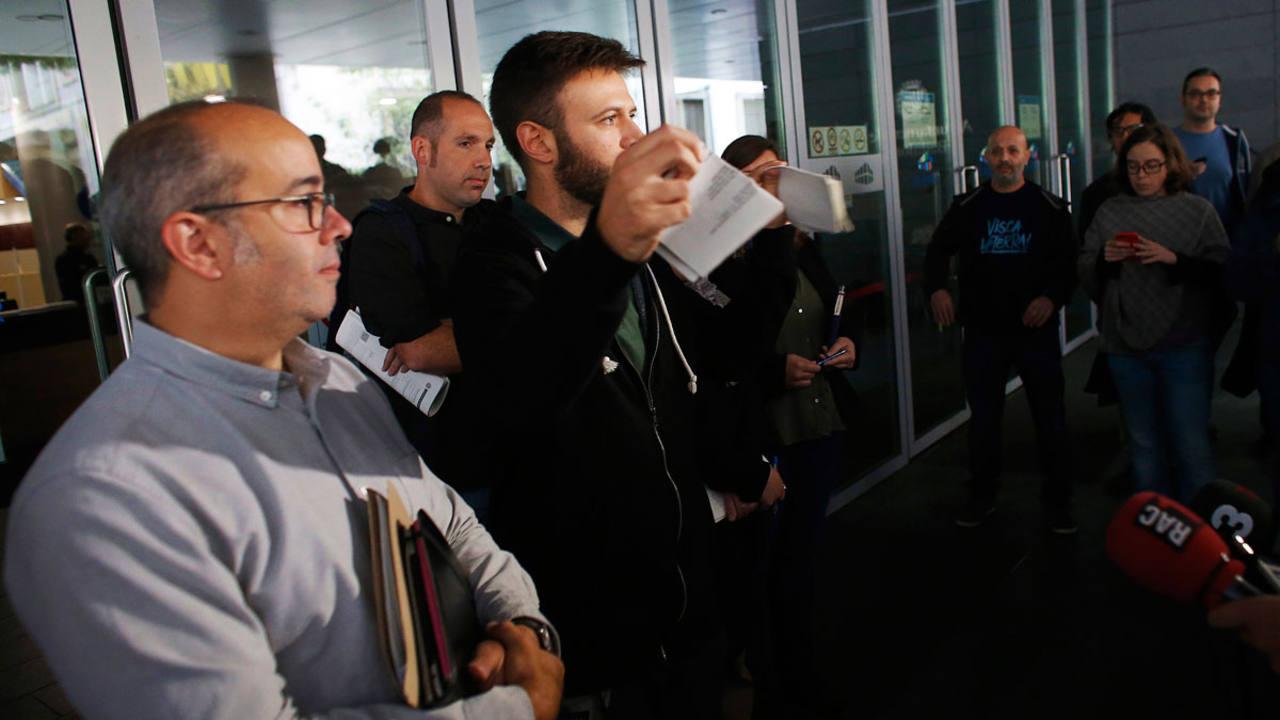 El primer teniente de alcalde y alcalde accidental de Badalona, Oriol Lladó a la izquierda, y el tercer teniente de alcalde, Josep Téllez, rompen el auto del juez que prohibía al Ayuntamiento abrir el 12 de octubre
