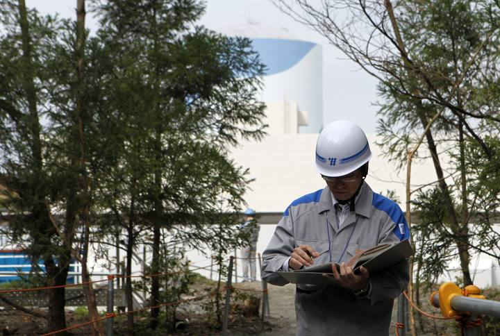 An employee of Kyushu Electric Power Co reads his memo at the company's Sendai nuclear power plant in Satsumasendai