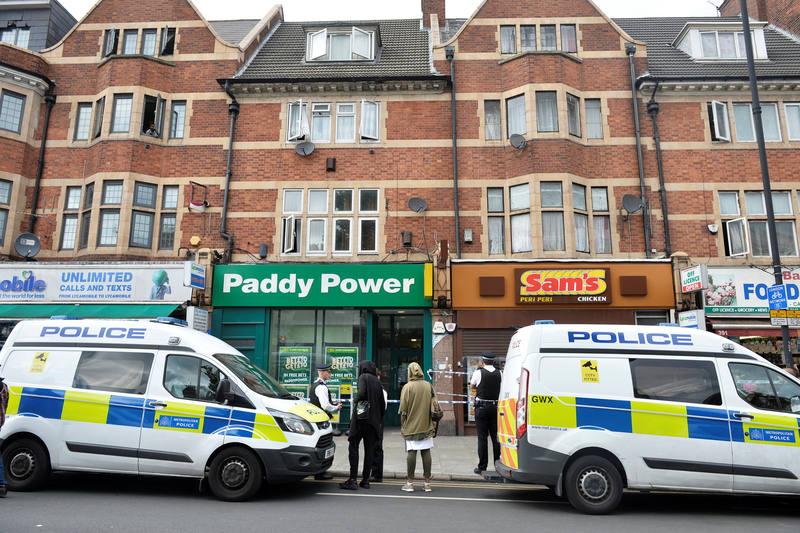 Agentes de policía permanecen frente a uno de los edificios donde se ha llevado a cabo un registro en Barking Road, Londres